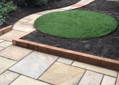 Sandstone patio and circular turf in Yate